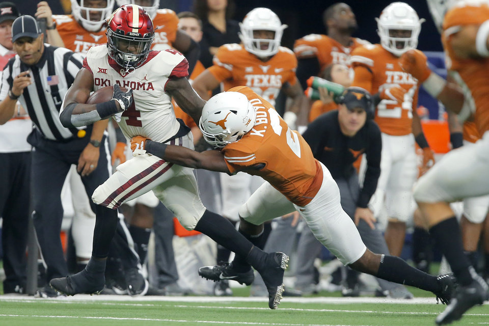 Photo - Oklahoma's Trey Sermon (4) runs past Kris Boyd (2) of Texas during the Big 12 Championship football game between the Oklahoma Sooners (OU) and the Texas Longhorns (UT) at AT&T Stadium in Arlington, Texas, Saturday, Dec. 1, 2018.  Oklahoma won 39-27. Photo by Bryan Terry, The Oklahoman