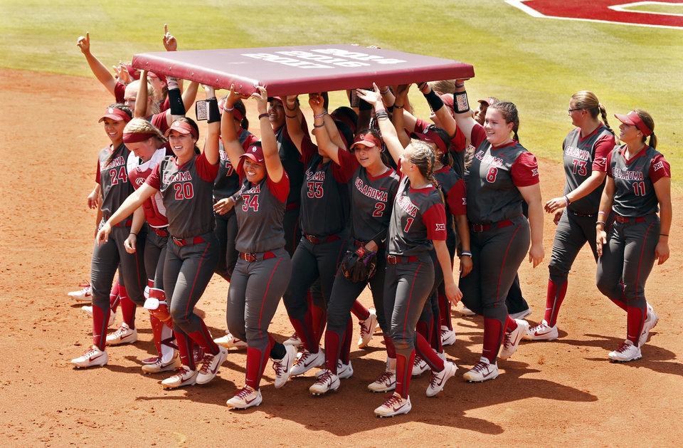 Photo - Players carry a piece of the outfield bumper to the infield for addition of another year of being World Series bound following the 2018 NCAA Championships Norman Super Regional Softball Game 2 where the University of Oklahoma Sooners (OU) defeated the Arkansas Razorbacks 9-0 at Marita Hynes Field at the OU Softball Complex on Saturday, May 26, 2018 in Norman, Okla.  Photo by Steve Sisney, The Oklahoman