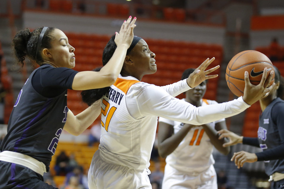 Photo - Oklahoma State's Ja'Mee Asberry (21) goes past TCU's Kianna Ray (25) during a women's NCAA basketball game between the Oklahoma State University Cowgirls (OSU) and the TCU Horned Frogs at Gallagher-Iba Arena in Stillwater, Okla., Wednesday, Jan. 29, 2020. Oklahoma State lost 72-68. [Bryan Terry/The Oklahoman]
