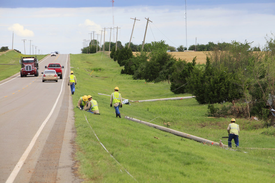 Photo - Tornado aftermath cleanup east of Piedmont, Wednesday, May 25, 2011. OG&E workers clear downed power lines on Sara Road that was hit by Tuesdays tornado. Photo by David McDaniel, The Oklahoman