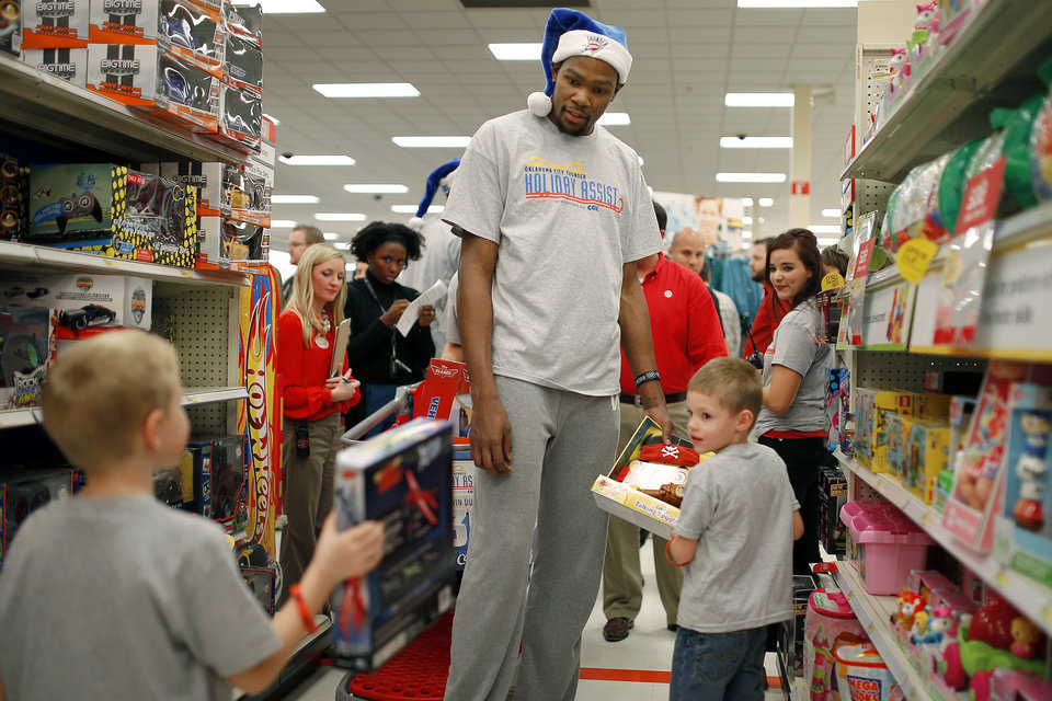 Photo - Kevin Durant, of the Oklahoma City Thunder, helps brothers Kaden, 6, at left, and Ladin Shippers, 5, pick out toys on Wednesday, December 18, 2013. The entire NBA team took 10 families directly affected by the Moore tornado on a shopping spree during the sixth annual event that is part of the Thunder Holiday Assist initiative. Photo by Bryan Terry, The Oklahoman