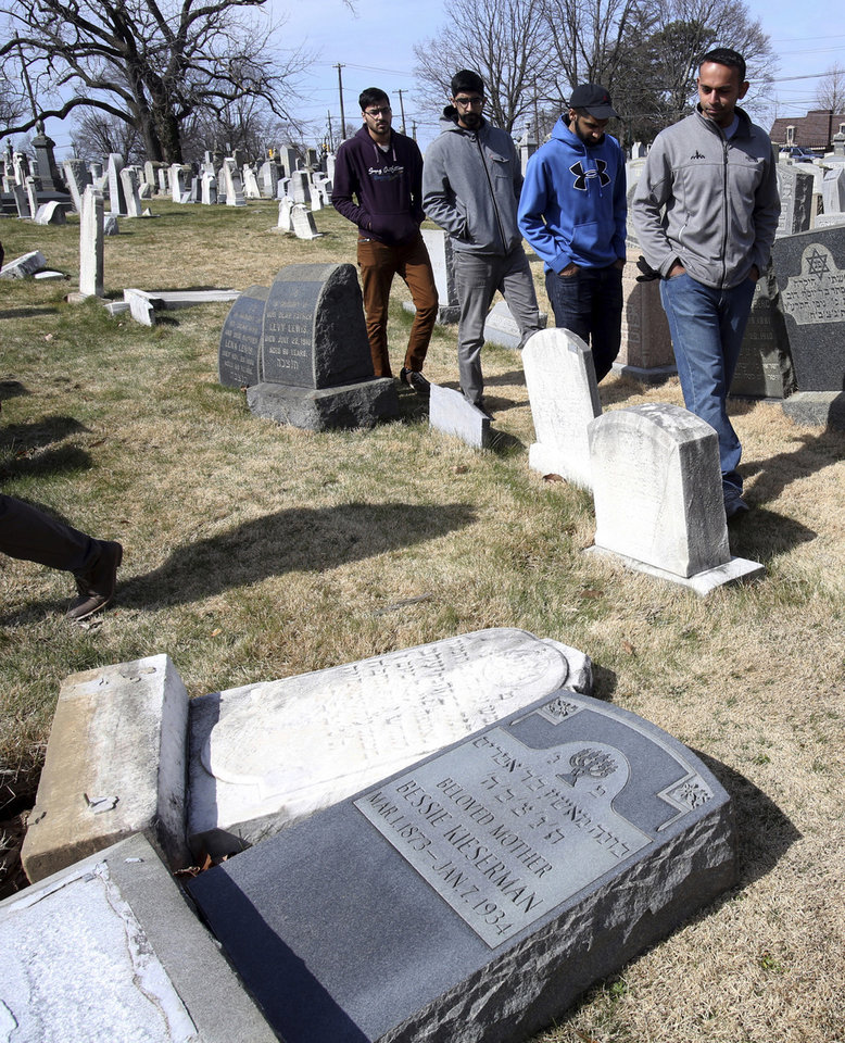 Photo - Volunteers from the Ahmadiyya Muslim Community survey damaged headstones at Mount Carmel Cemetery on Monday, Feb. 27, 2017, in Philadelphia. More than 100 headstones have been vandalized at the Jewish cemetery in Philadelphia, damage discovered less than a week after similar vandalism in Missouri, authorities said. (AP Photo/Jacqueline Larma)