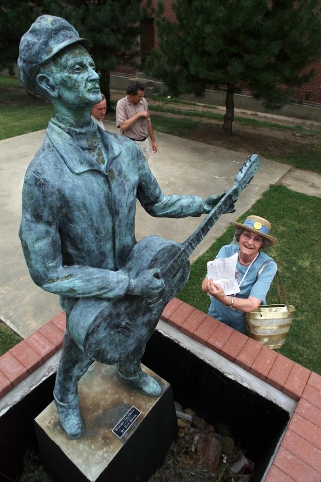 Photo - Woody Guthrie's sister Mary Jo Guthrie Edgmon, of Seminole, stops by the statue of her brother in a downtown Okemah park during the 2001 Woody Guthrie Festival. She is holding a letter placed behind the statue's guitar by an admirer. Edgmon died March 16 at the age of 96. The Oklahoman Archives photo