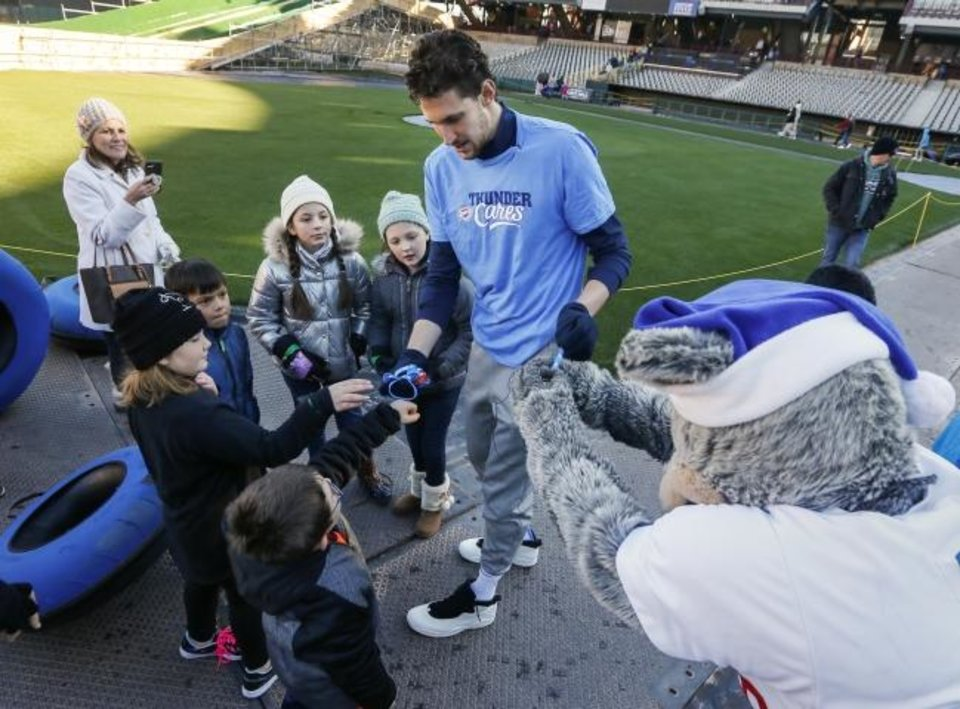 Photo -  Oklahoma City Thunder player Mike Muscala hands out wristbands, including one to Oklahoma City Dodgers mascot Brix, right, during a visit by Thunder basketball players to the LifeShare WinterFest at Chickasaw Bricktown Ballpark in Oklahoma City, Monday, Dec. 30, 2019. [Nate Billings/The Oklahoman]