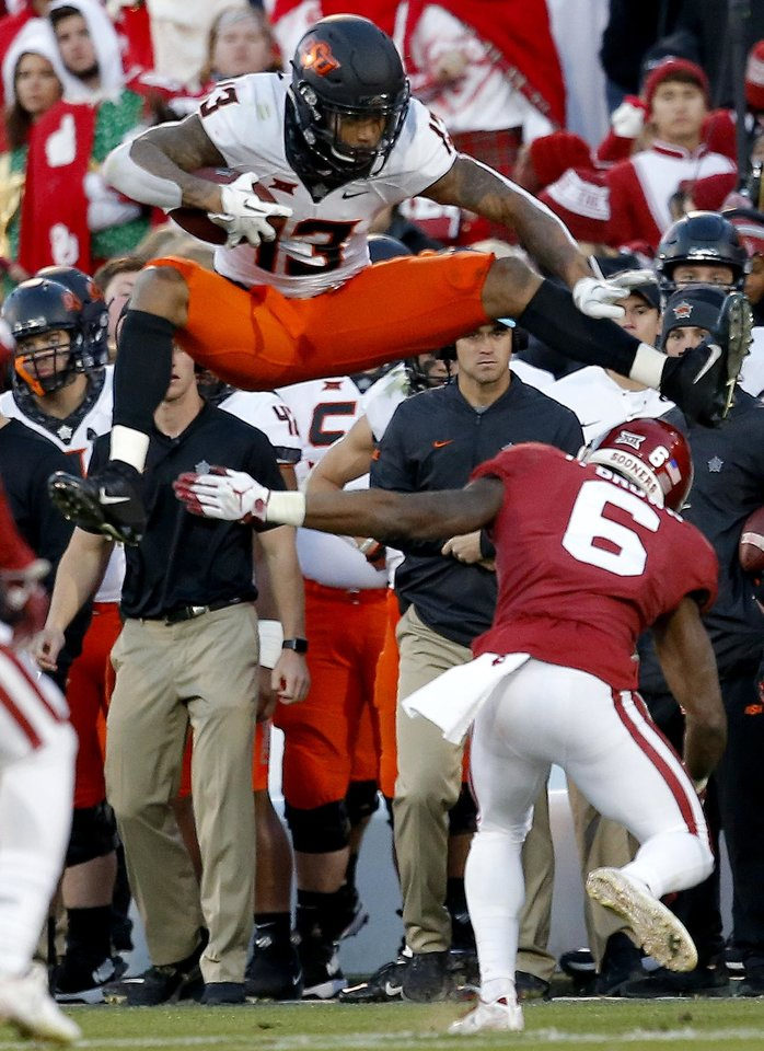 Photo - Oklahoma State's Tyron Johnson (13) leaps over Oklahoma's Tre Brown (6) in the third quarter during a Bedlam college football game between the University of Oklahoma Sooners (OU) and the Oklahoma State University Cowboys (OSU) at Gaylord Family-Oklahoma Memorial Stadium in Norman, Okla., Nov. 10, 2018.  OU won 48-47. Photo by Sarah Phipps, The Oklahoman