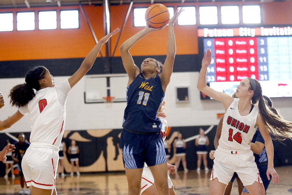 Photo - Putnam City West's Zaniya Nelson shoots as Union's Taklya Pitts (0) and Union's Makenzie Malham (14) during the girls championship game between Putnam City West and Tulsa Union at the Putnam City Invitational at Putnam City High School in Oklahoma City, Okla.,  Saturday, Jan. 11, 2020.  [Sarah Phipps/The Oklahoman]
