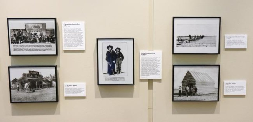 Photo -  Photographs of drinking establishments surround an image of petty thieves Cattle Annie and Little Britches in the Oklahoma History Center's exhibit