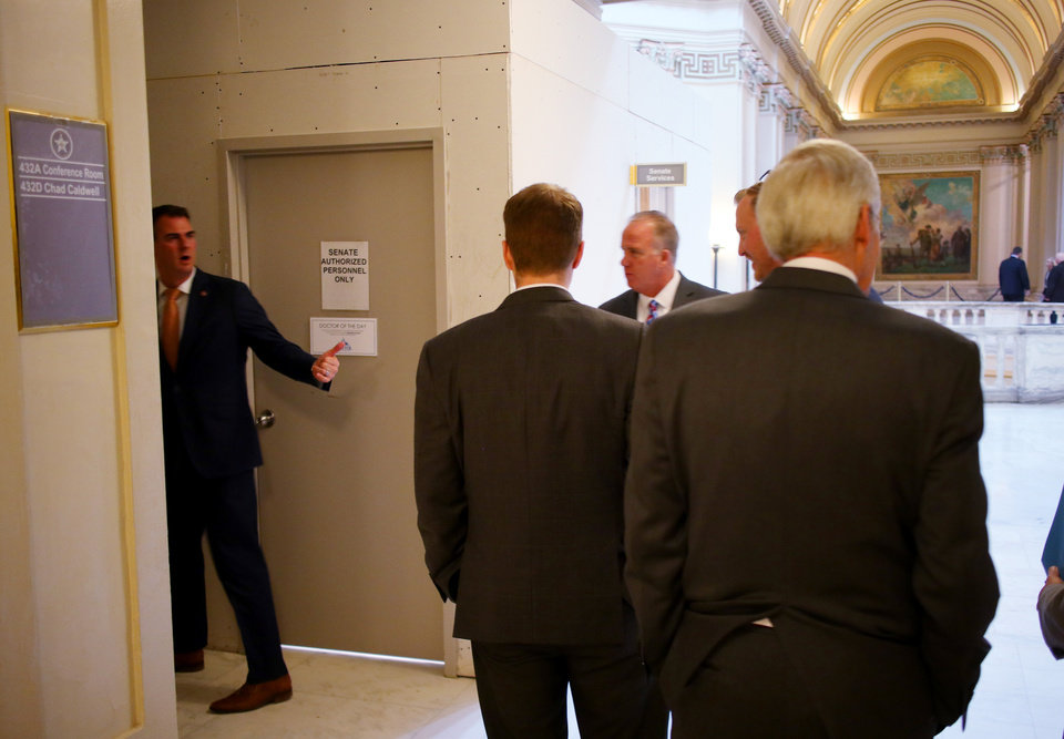 Photo - Gov. Kevin Stitt visits with legislators in the hall after a press conference announcing his first executive orders at the Capitol Thursday, January 24, 2019.  Photo by Doug Hoke, The Oklahoman