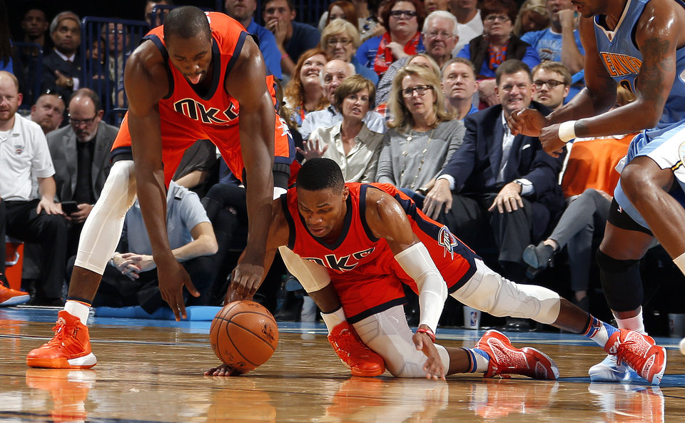 Photo - Oklahoma City's Serge Ibaka (9) and Russell Westbrook (0) scramble for a loos ball during the NBA game between the Oklahoma City Thunder and the Denver Nuggets at the Chesapeake Energy Arena , Sunday, Nov. 1, 2015. Photo by Sarah Phipps, The Oklahoman