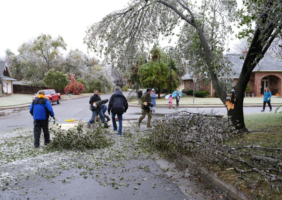 Photo - Neighbors work together to clear tree limbs that fell blocking Chimney Hill Rd at Brixton Rd  from the ice storm that hit the Oklahoma City metro area Tuesday, October 27, 2020. [Doug Hoke/The Oklahoman]