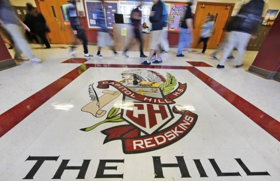 Photo - Students walk past the Capitol Hill High School logo in Oklahoma City.  On Friday, May 22, the Oklahoma City school is expected to announce its nickname change. The Oklahoma City Public Schools Board voted to change the schools mascot from Redskins in December 2014. Photo By Steve Gooch, The Oklahoman