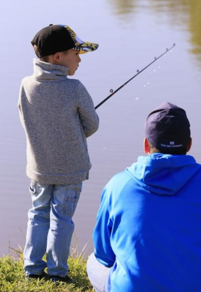 Photo -  Jeffrey Echeverry watches as his son, Ethan, fishes at Edwards Park Lake in Oklahoma City two years ago as part of Parks and Recreation Department's youth fishing class. [Oklahoman Archives]
