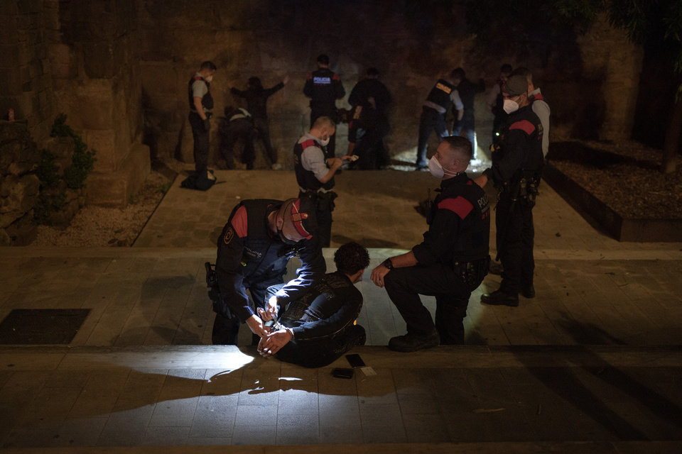 Photo -  People are detained and inspected by Mossos D'Esquadra, the regional police of Catalonia, after curfew in Barcelona, Spain, Sunday, Nov. 1, 2020. Despite a large adherence to the recently re-imposed curfews in Spain, police patrolling Barcelona are still finding young people breaking the rules. (AP Photo/Emilio Morenatti)