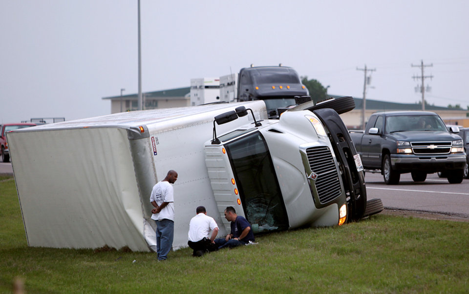 Photo - Northbound traffic passes a truck that was blown over during a storm on I-35 near  Hillsdale Free Will Baptist College in Norman on Monday, May 10, 2010. By John Clanton, The Oklahoman
