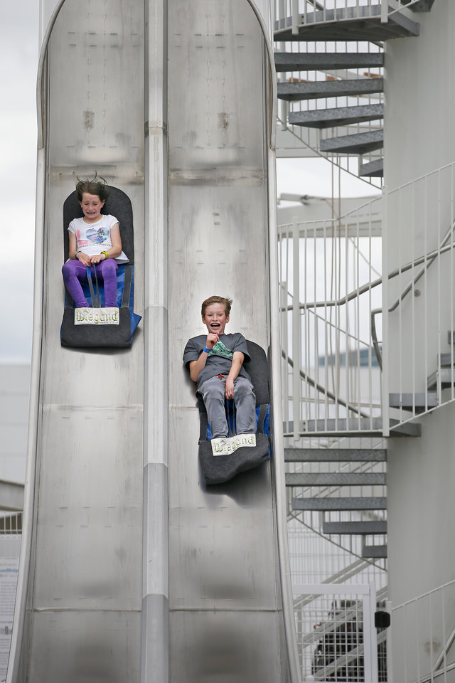 Photo -  Emma Pekrul, 8, and her brother Cooper Pekrul, 12, race down a slide at Riversport Adventures on Tuesday. Riversport Adventures. [Bryan Terry/The Oklahoman]