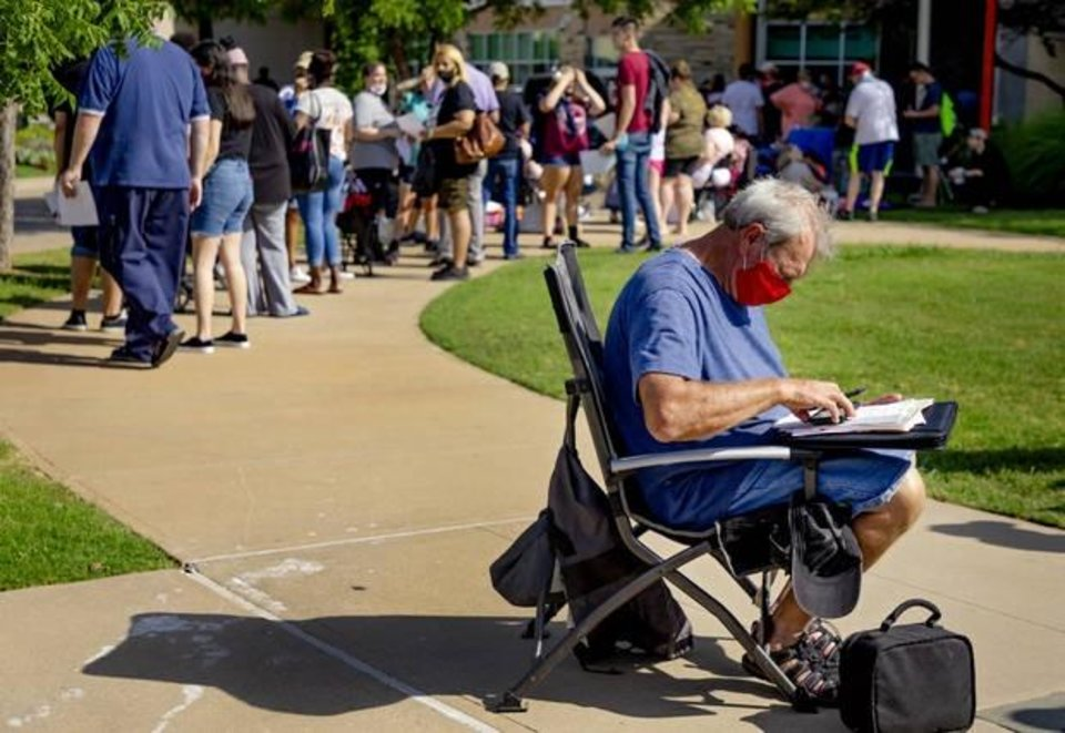 Photo -  Larry Self works to fill out paperwork Wednesday as he waits in line with hundreds of people during the first day of the Oklahoma Employment Security Commission unemployment filing event at the Reed Center in Midwest City.  [Chris Landsberger/The Oklahoman]