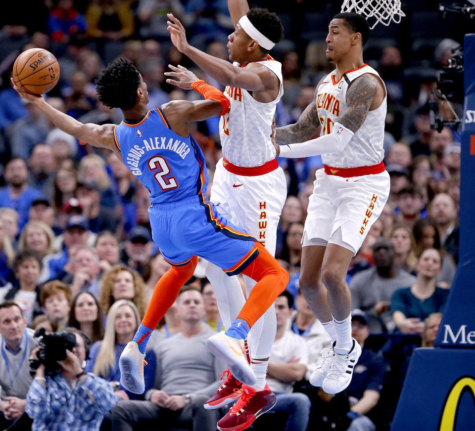 Photo - Oklahoma City's Shai Gilgeous-Alexander (2) goes up for a lay up as Atlanta's De'Andre Hunter (12) and John Collins (20) defend during the NBA basketball game between the Oklahoma City Thunder and the Atlanta Hawks at the Chesapeake Energy Arena in Oklahoma City,Friday, Jan. 24, 2020.  [Sarah Phipps/The Oklahoman]