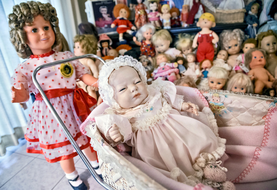 Photo -  A 50th Edition Shirley Temple Doll stands near a baby doll in a buggy surrounded by other pieces of Imogene McDowell's collection of more than 500 dolls at her Mustang home. [Photo by Chris Landsberger, The Oklahoman]