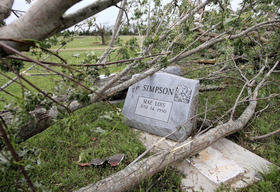 Photo - A large tree limb,  toppled by Monday night's tornado, removed this headstone from its base on a grave in Earlsboro Cemetery on Highway 9A in  Pottawatomie County.  Photo taken Wednesday, May 12, 2010.  Many headstones in the cemetery were knocked over when the twister crossed through the area.  Photo by Jim Beckel, The Oklahoman