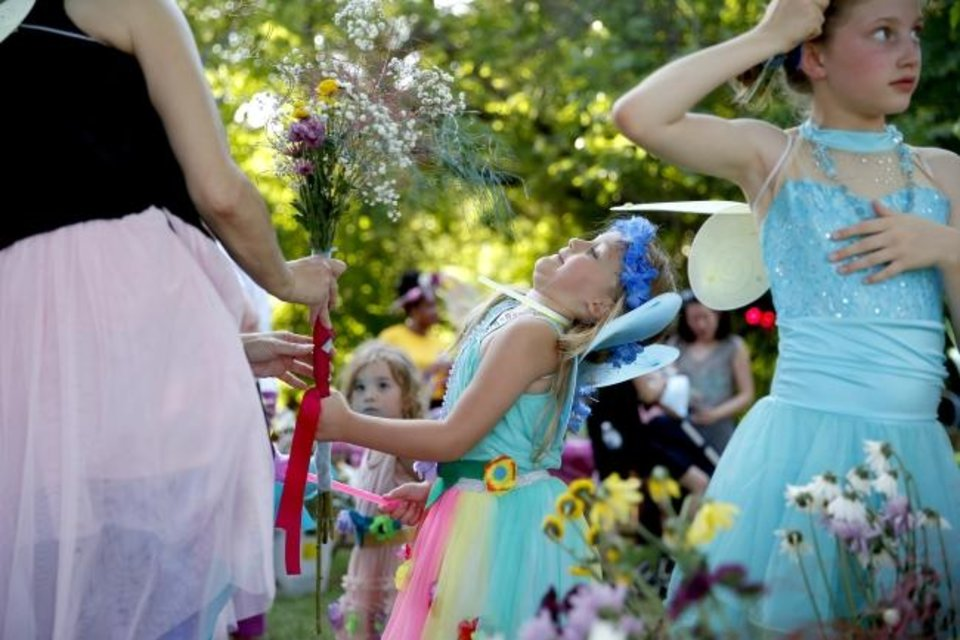 Photo -  Lily Sue Ortega, 5, pulls her head back as her grandmother, Jacquelyn Ortega, hands her flowers during the ball.