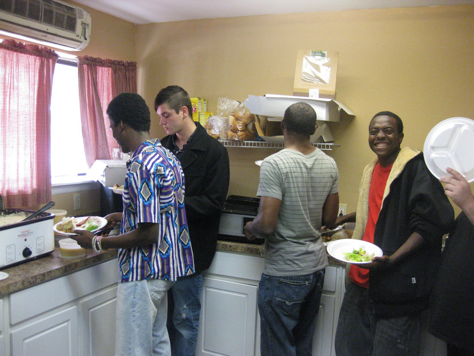 Photo - Men help themselves to Thanksgiving dinner in the residential size kitchen currently serving about 20 young men at Neighborhood Services Organization's Carolyn Williams Center. A new kitchen is in the plannning, to be funded by a $100,000 grant to the center from Impact Oklahoma. Photo provided.