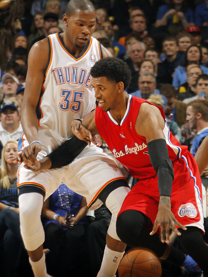 Photo - Oklahoma City Thunder small forward Kevin Durant (35) defends on Los Angeles Clippers shooting guard Nick Young (11) during the NBA basketball game between the Oklahoma City Thunder and the Los Angeles Clippers at Chesapeake Energy Arena on Wednesday, March 21, 2012 in Oklahoma City, Okla.  Photo by Chris Landsberger, The Oklahoman