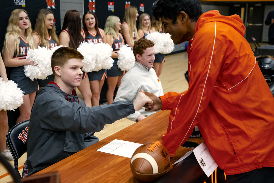 Photo - University of Oklahoma signee Cade Horton, left, celebrates signing his letter of intent with classmates during a national signing day ceremony for football at Norman High School in Norman Okla. on Wednesday, Dec. 18, 2019.   [Chris Landsberger/The Oklahoman]