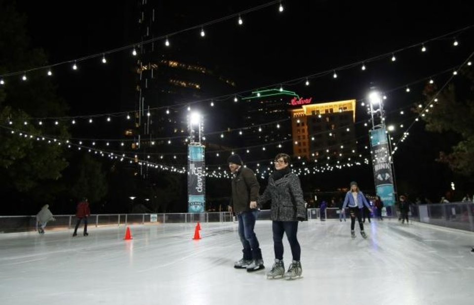 Photo -  Peggy and Terry Hood skate at the Devon Ice Rink on the seasonal plaza of the Myriad Botanical Gardens. [Doug Hoke/The Oklahoman]