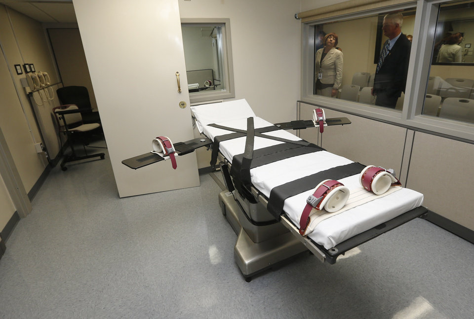 Photo - In this Oct. 9, 2014 file photo, Department of Corrections officials are pictured in the witness room at right, outside the newly renovated death chamber at the Oklahoma State Penitentiary in McAlester, Okla. (AP Photo/Sue Ogrocki, File)