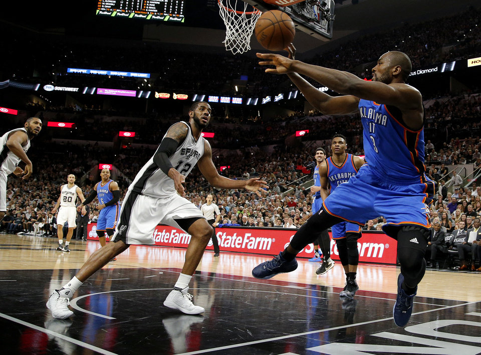 Photo - Oklahoma City's Serge Ibaka (9) tries to keep the ball in play beside San Antonio's LaMarcus Aldridge (12) during Game 5 of the second-round series between the Oklahoma City Thunder and the San Antonio Spurs in the NBA playoffs at the AT&T Center in San Antonio, Tuesday, May 10, 2016. Oklahoma City won 95-91. Photo by Bryan Terry, The Oklahoman