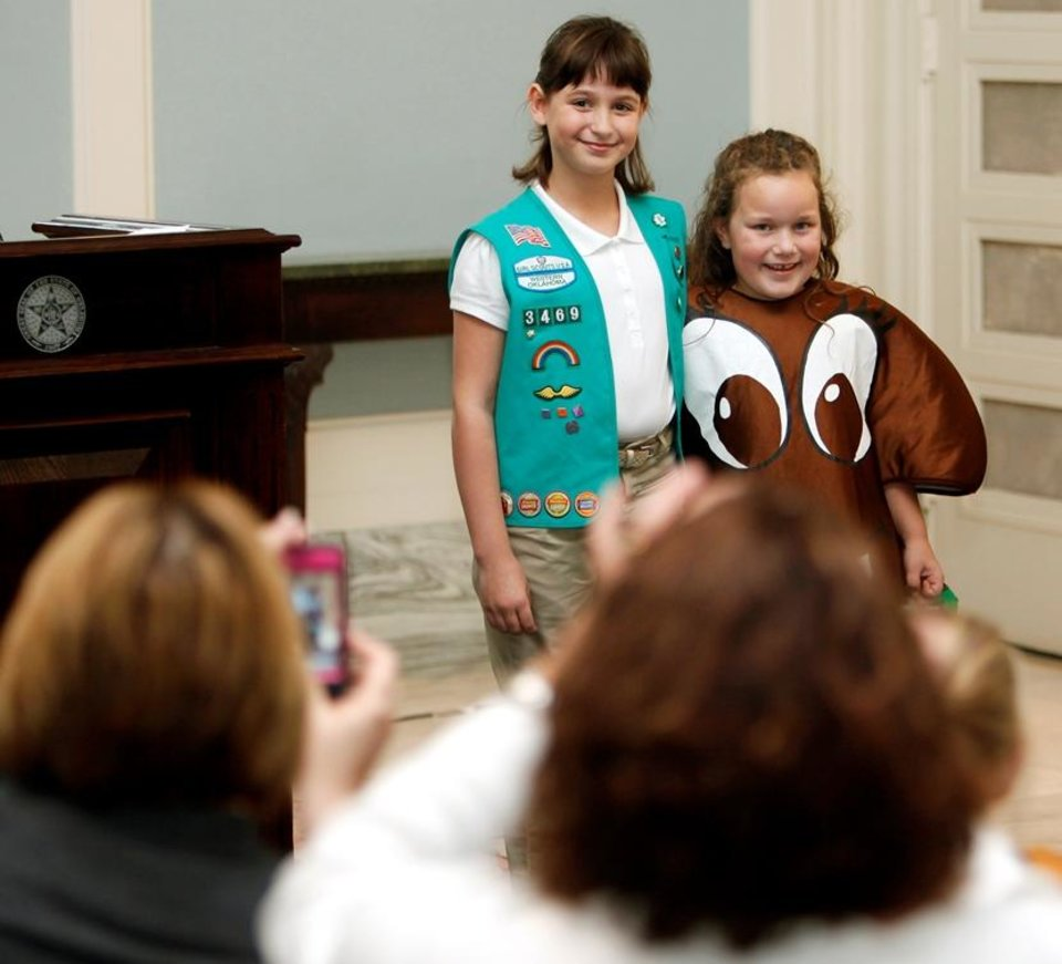 Photo - Girl Scout Katie Francis, the top Girl Scout Cookie seller in the state this year, left, poses in 2012 with fellow Girl Scout Piper Bush, wearing a Thin Mints costume, during a ceremony for the Oklahoma's Favorite Girl Scout Cookie Contest at the state Capitol in Oklahoma City. Francis was awarded a $1,529 Oklahoma 529 College Savings Plan account during the ceremony for selling 7,482 boxes of cookies, an all-time state record. She has gone on to break the national records for most cookies sold in a single season and most cookies sold in a Girl Scout career. Photo by Nate Billings, The Oklahoman Archives