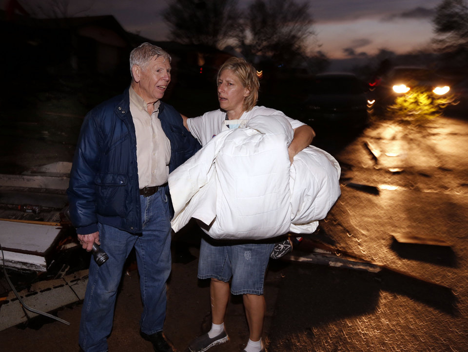 Photo - A family member of his across the street neighbor checks on Morris Moore after tornado force winds blew roofs off houses on Main Street near Janeway on Wednesday, March 25, 2015 in Moore, Okla. Photo by Steve Sisney, The Oklahoman