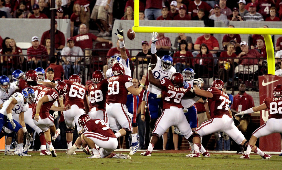 Photo - Michael Hunnicutt (18) kicks an extra point during the college football game between the University of Oklahoma Sooners (OU) and the University of Kansas Jayhawks (KU) at Gaylord Family-Oklahoma Memorial Stadium in Norman, Okla., on Saturday, Oct. 20, 2012. Photo by Steve Sisney, The Oklahoman