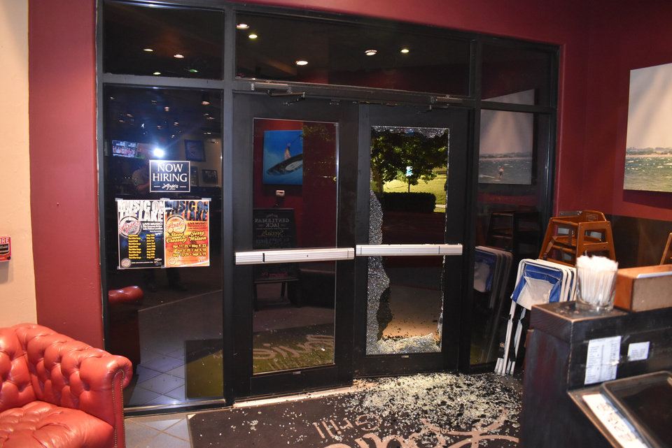 Photo -  This police evidence photo shows the shattered front door at Louie's Grill & Bar at Lake Hefner. [Photo Provided]