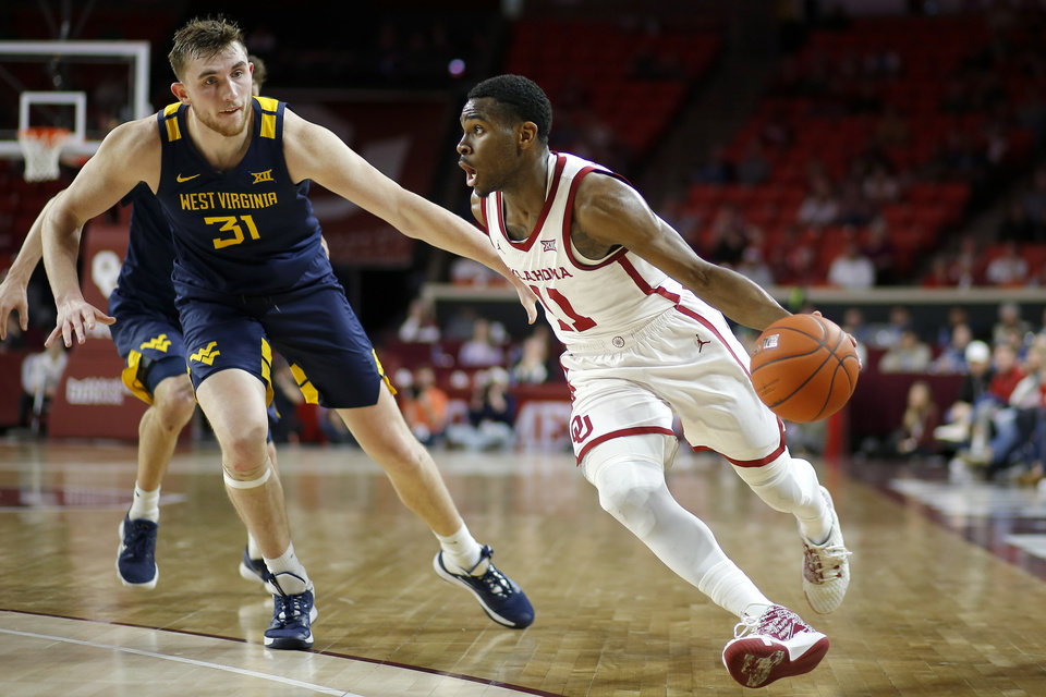 Photo - Oklahoma's De'Vion Harmon (11) goes past West Virginia's Logan Routt (31) during an NCAA mens college basketball game between the University of Oklahoma Sooners (OU) and the West Virginia Mountaineers at the Lloyd Noble Center in Norman, Okla.,Saturday, Feb. 8, 2020. [Bryan Terry/The Oklahoman]