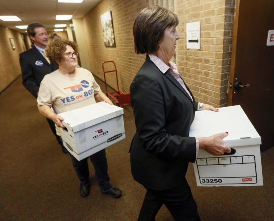 Photo -  Patti Davis, president of the Oklahoma Hospital Association, leads supporters of Yes on 802, the campaign to put a Medicaid expansion state question on the ballot, as they deliver petitions to the Oklahoma secretary of state's office in Oklahoma City on Thursday. [Nate Billings/The Oklahoman]