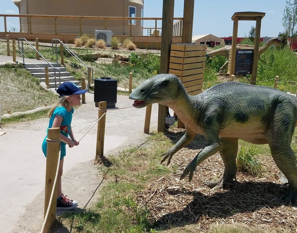 Photo -  Brenna McDonnell, 8-year-old daughter of Features Writer Brandy McDonnell, looks at a life-sized Claosaurus at Field Station: Dinosaurs in Derby, Kansas. [Photo by Brandy McDonnell, The Oklahoman]