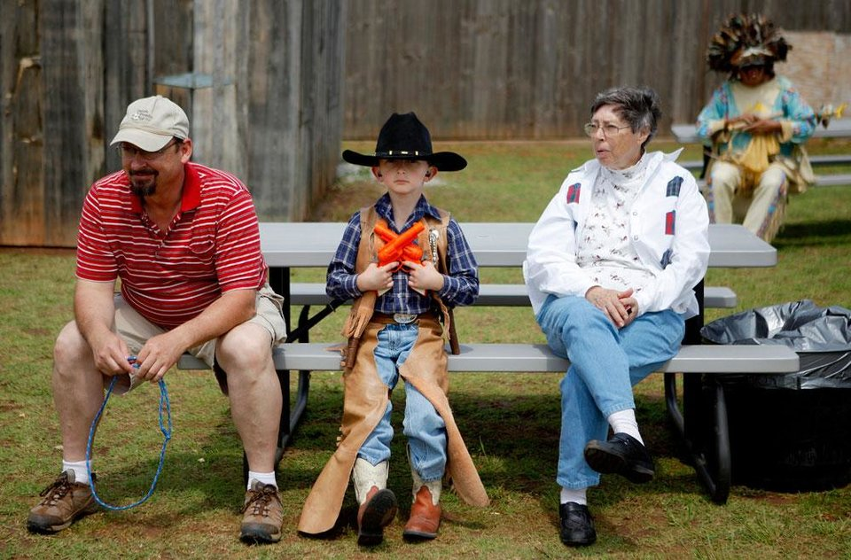 Photo -  J.W. Struck, 7, sits between his father David Struck, left, and grandmother Ora Struck during Kingfisher's Living History Days at the Chisholm Trail Museum in Kingfisher, Okla., Saturday, April 14, 2012. Photo by Bryan Terry, The Oklahoman