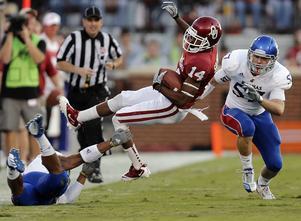 Photo - OU's Jalen Saunders (14) is tripped up by a Kansas defender during the college football game between the University of Oklahoma Sooners (OU) and the University of Kansas Jayhawks (KU) at Gaylord Family-Oklahoma Memorial Stadium on Saturday, Oct. 20th, 2012, in Norman, Okla. Photo by Chris Landsberger, The Oklahoman