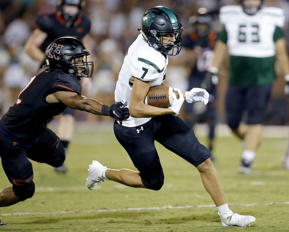 Photo - Norman North's Cale Cabbiness runs with the ball as Norman's Corterius Smith defends during a game at Gaylord Family-Oklahoma Memorial Stadium in Norman on Sept. 5. [Sarah Phipps/The Oklahoman]