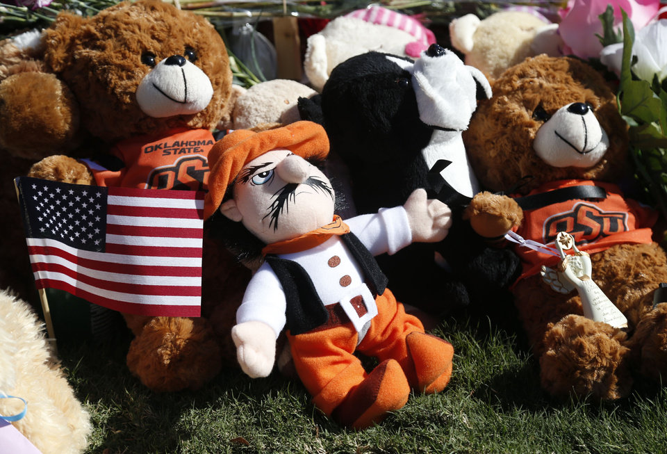 Photo -  Stuffed animals and other items are placed at a roadside memorial to victims of a fatal car crash near Oklahoma State University in Stillwater, Okla., on Sunday, October 25, 2015. Four people were killed when a driver crashed her car into a crowd during the university's homecoming parade. MATT BARNARD/Tulsa World