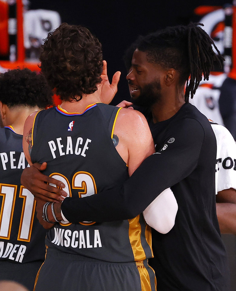 Photo - Nerlens Noel hugs Mike Muscala, left, of the Oklahoma City Thunder after Muscala hit the game-winning three-point basket against the Miami Heat during the second half of an NBA basketball game Wednesday, Aug. 12, 2020, in Lake Buena Vista, Fla. (Kevin C. Cox/Pool Photo via AP)