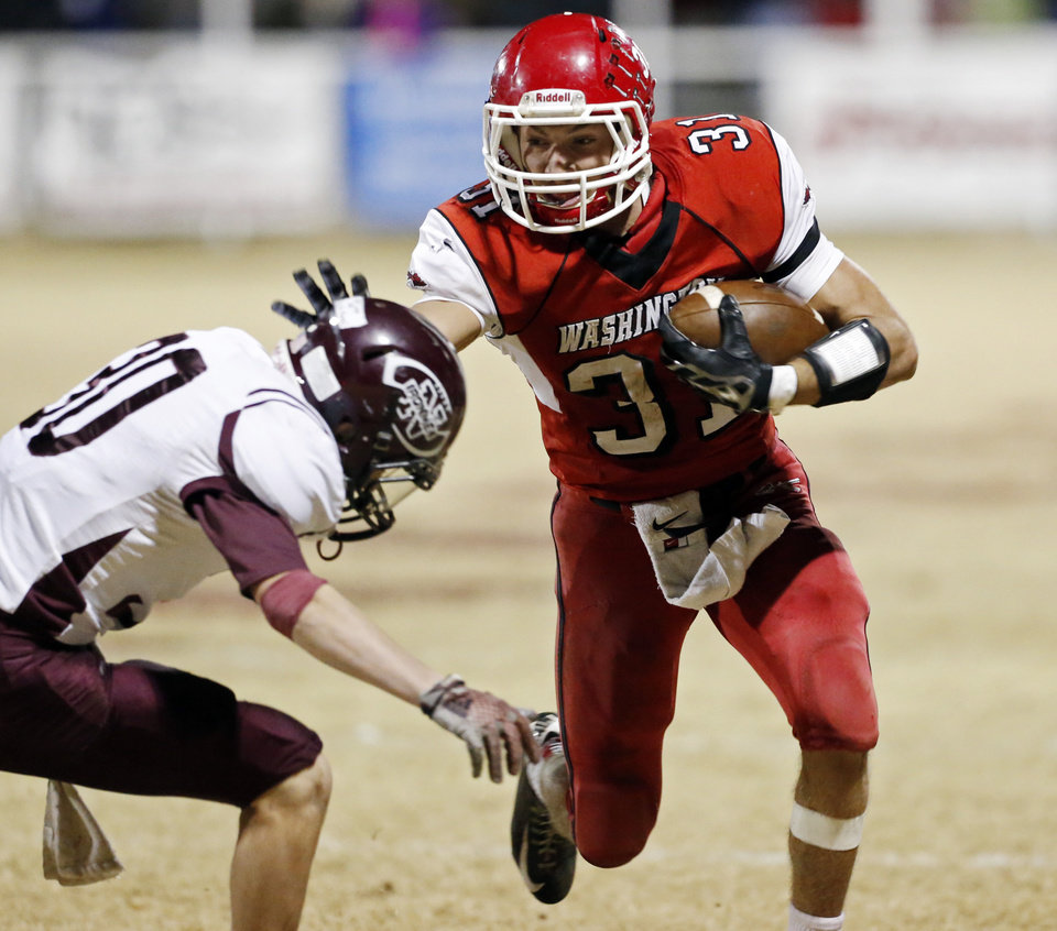 Photo - Washington's Clollin Andrews tries to avoid Ethan Foster as the Nowata Ironmen play the Washington Warriors in high school football on Friday, Nov. 28, 2014 in Washington, Okla. Photo by Steve Sisney, The Oklahoman