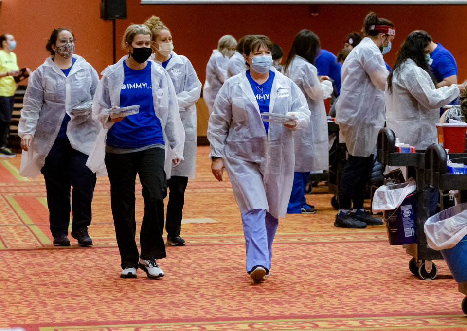 Photo - Members of IMMY Labs prepare to administer inoculations during a Covid-19 vaccination pod at the Embassy Suites by Hilton Norman Hotel & Conference Center in Norman, Okla. on Monday, Feb. 22, 2021.  [Chris Landsberger/The Oklahoman]