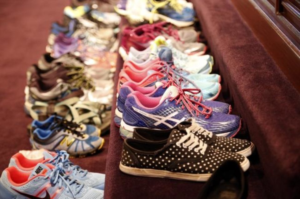 Photo -  Shoes sit on the altar during the 2016 Blessing of the Shoes and Gloves service at First Church in downtown Oklahoma City.  [Sarah Phipps/The Oklahoman]