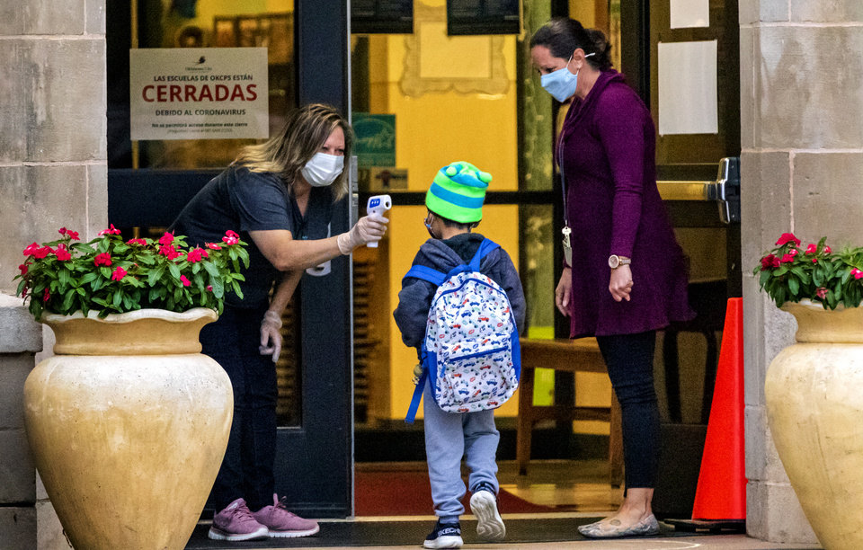 Photo - Hawthorne Elementary principal Melinda Elms, right, looks on as a student has their temperature taken as Pre-K and kindergarten students arrive for the first day of in person class at Hawthorne Elementary in Oklahoma City, Okla. on Tuesday, Oct. 20, 2020. Oklahoma City Public Schools welcomed Pre-K and kindergarten students back to class as the first phase bringing students back to the classroom, and will bring back older students Nov. 9th.   [Chris Landsberger/The Oklahoman]