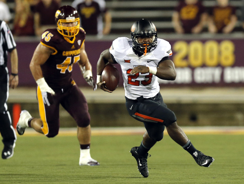 Photo - Oklahoma State's Rennie Childs (23) rushes as Central Michigan's Joe Ostman (45) chases him down during the college football game between the Central Michigan Chippewas and the Oklahoma State University Cowboys at the Kelly-Shorts Stadium in Mount Pleasant, Mich., Thursday, Sept. 3, 2015. Photo by Sarah Phipps, The Oklahoman