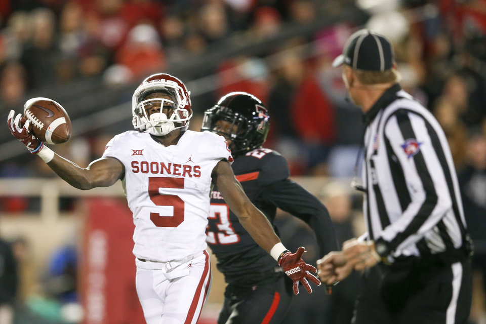 Photo - Oklahoma Sooners wide receiver Marquise Brown (5) attempts to haul in a catch one handed while being defende by Texas Tech Red Raiders defensive back Damarcus Fields (23) during the NCAA football game between the Texas Tech Red Raiders and the Oklahoma Sooners at Jones AT&T Stadium in Lubbock, Texas on Saturday, November 03, 2018. IAN MAULE/Tulsa World