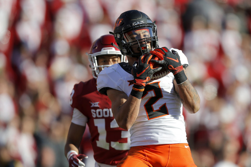 Photo - Oklahoma State's Tylan Wallace (2) catches a touchdown pass in front of Oklahoma's Tre Norwood (13) during a Bedlam college football game between the University of Oklahoma Sooners (OU) and the Oklahoma State University Cowboys (OSU) at Gaylord Family-Oklahoma Memorial Stadium in Norman, Okla., Nov. 10, 2018.  Photo by Bryan Terry, The Oklahoman