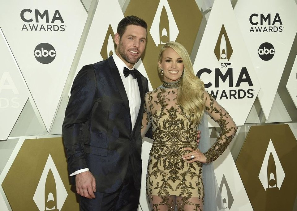 Photo - Mike Fisher, left, and Carrie Underwood arrive at the 53rd annual CMA Awards at Bridgestone Arena on Wednesday, Nov. 13, 2019, in Nashville, Tenn. [Photo by Evan Agostini/Invision/AP]